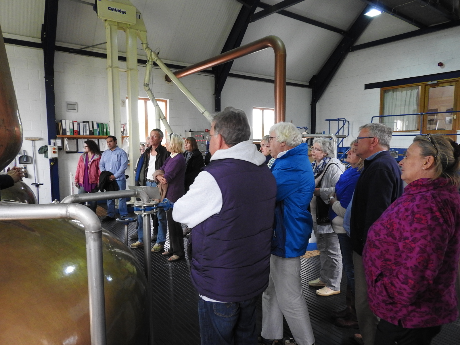 People listening to a man talking about whisky